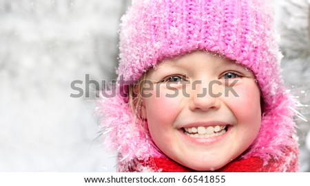 Little happy girl in winter pink hat in snow forest. - stock photo