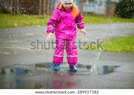 Little happy girl jumping and having fun in puddle - stock photo