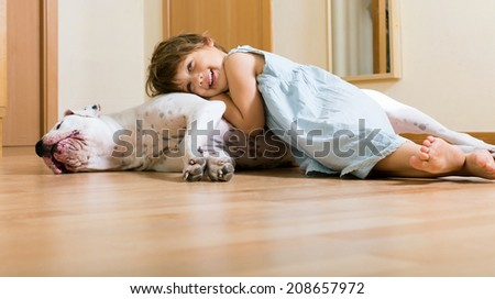 little happy girl on the floor with dogo Argentino (focus on dog) - stock photo