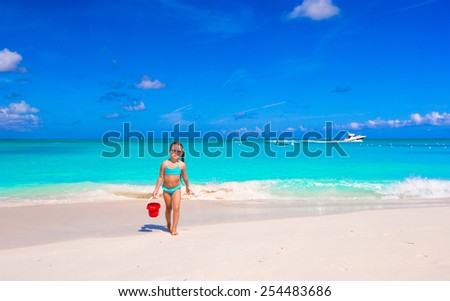 Little happy girl playing with beach toys during tropical vacation - stock photo