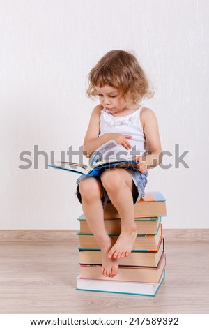 Little happy girl sits on a heap of books in a room and reads. Early development and learning. - stock photo