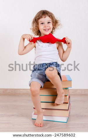 Little happy girl sits on a heap of books in a room with a toy. Early development and learning. - stock photo