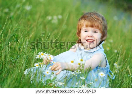 little happy girl with chamomile daisy on summer field - stock photo