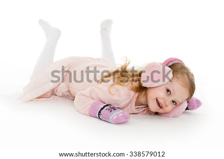 Little happy pretty girl in winter clothes lies on a white background. 3 year old. - stock photo