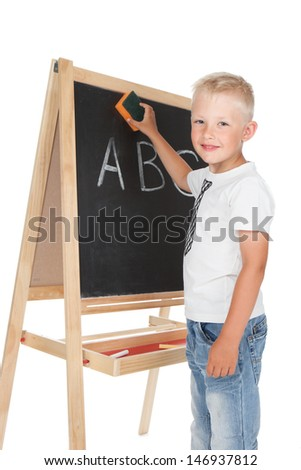 Little happy schoolboy writing on a blackboard over white - stock photo