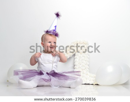 Little happy toddler baby girl celebrating first birthday sitting with big 1 sign made of patchwork roses and white balloons - stock photo