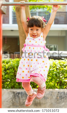 little healthy girl hanging on a bar - stock photo
