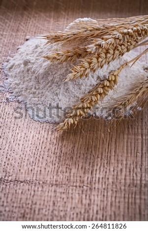 little heap of flour and ears of wheat on wooden board on wooden board food and drink still life  - stock photo
