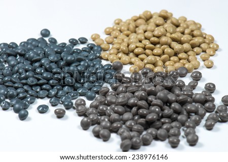 little heaps of grey and brown polymer granulate on white  - stock photo