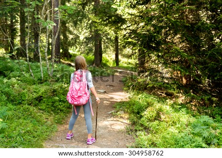 Little hiker girl in forest. Photo from Champex-Lac, Valais, swiss Alps, back view - stock photo