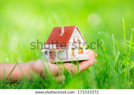 Little house in children`s hand against green spring background. Shallow depth of field