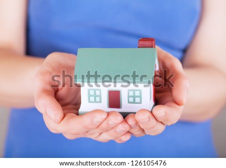 Little house toy in woman's hands - stock photo