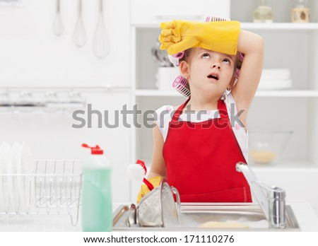 Little housekeeping fairy girl tired of home chores - doing the dishes - stock photo