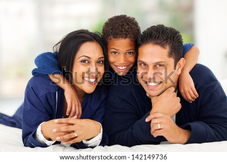little indian boy hugging his parents while lying on bed - stock photo