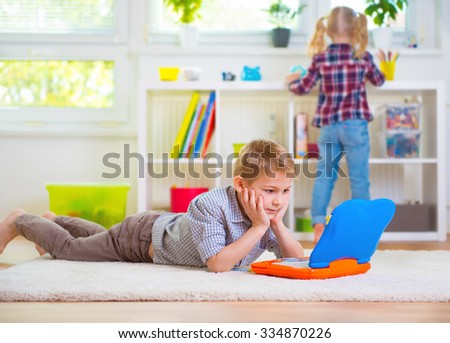 Little intelligent boy play with toy laptop at home - stock photo