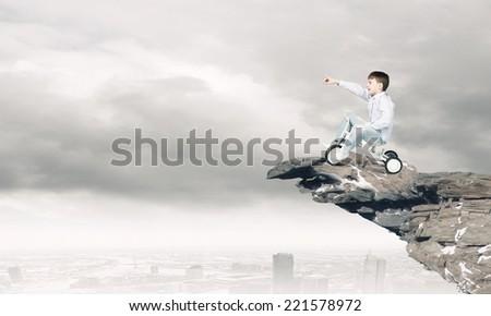 Little joyful cute boy riding tricycle on cliff edge - stock photo