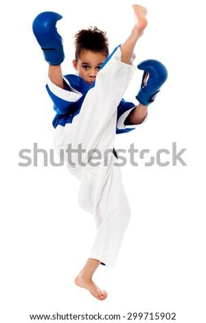 Little karate kid kicking by a leg - stock photo