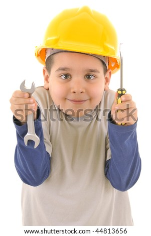 Little kid as a construction worker wearing yellow helmet with a screwdriver and wrench in his hands.White background vertical studio picture.