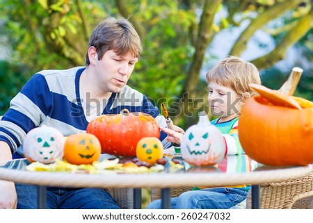 Little kid boy and his father making traditional jack-o-lantern for halloween in autumn garden, outdoors. Family having fun together - stock photo