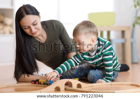 Little kid boy and his mother playing with railway sitting on the floor.