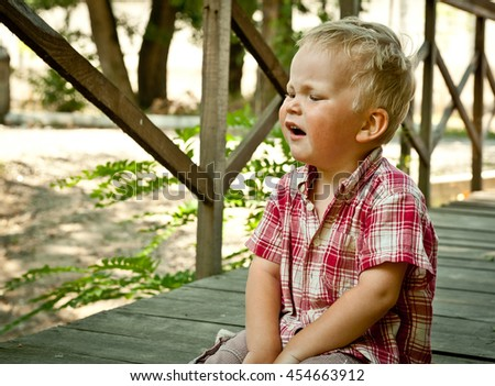 Little kid Boy crying sitting on steps in park. Loneliness, melancholy, stress, bullying, depression or frustration. Upset crying tears problem child toddler with blond hairstyle  with head in hands - stock photo