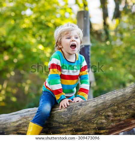 Little kid boy in colorful shirt with stripes and gumboots having fun with playing on playground on warm, autumn day, outdoors. Family, happy childhood,  kids concept - stock photo