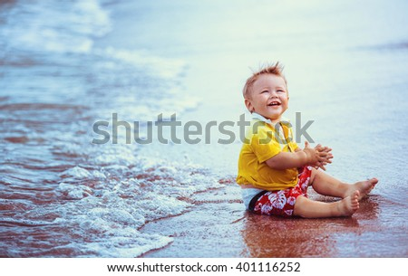Little kid, boy in yellow shirt, red shorts, sitting on the beach close to  water, playing laughing, smiling - stock photo