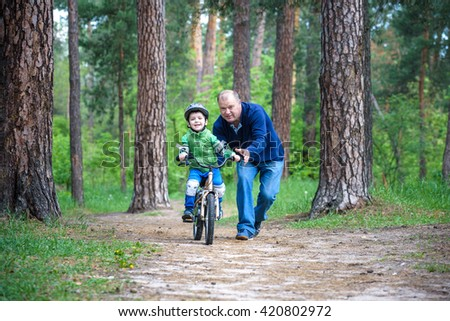 Little kid boy of 3 years and his father in autumn forest with a bicycle. Dad teaching his son. Man happy about success. Child with helmet. Safety, sports, leisure with kids concept. - stock photo