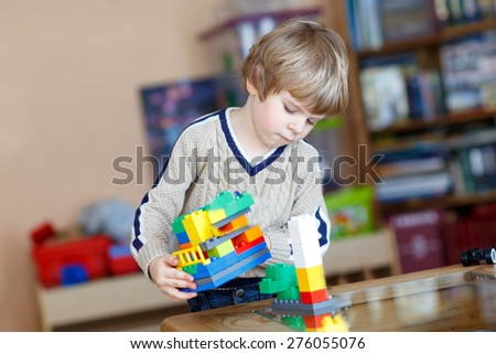 Little kid boy playing with lots of colorful plastic blocks indoor. Child having fun with building and creating. - stock photo