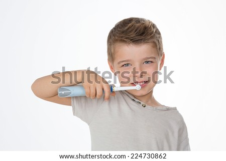little kid cleans his teeth with electric toothbrush - stock photo