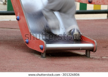 little kid climbing on a slide, from backside - stock photo
