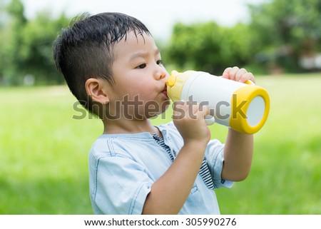 Little kid drink of water bottle - stock photo