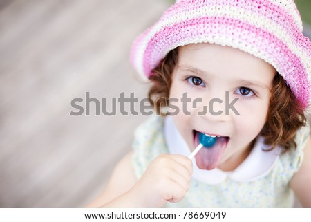 Little kid enjoying a lollypop while staring at camera from below - stock photo