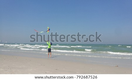 little kid flying the kite by the beach