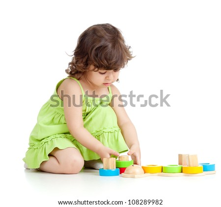 little kid girl playing with colorful toys, isolated over white - stock photo