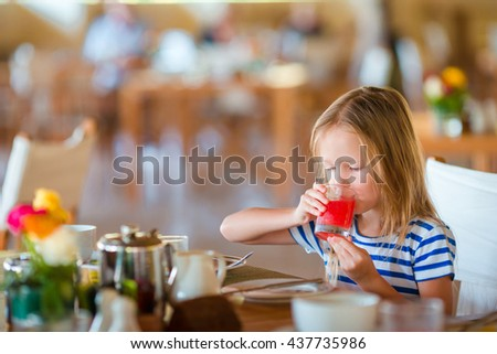 Little kid having breakfast at outdoor cafe. Adorable girl drinking fresh watermelon juice enjoying breakfast.