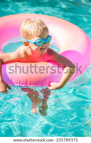 Little Kid Having Fun in Swimming Pool, with Goggles and Raft. Summer Vacation Fun. - stock photo
