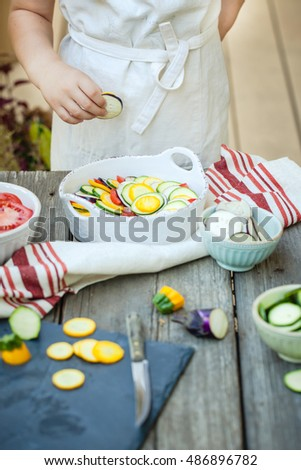 Little kid, helping to prepare ratatouille - French vegetable dish.