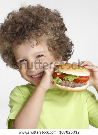 Little kid holding a big hamburger,eating hamburger. - stock photo