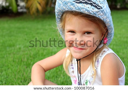 little kid in a cowboy hat with a grin and a bruise on his forehead, - stock photo