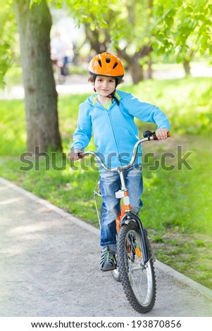 Little kid in blue jacket cycling in a suburban recreation area