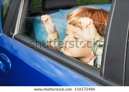 little kid is sitting sad on the back sit and look tired of car trip - stock photo