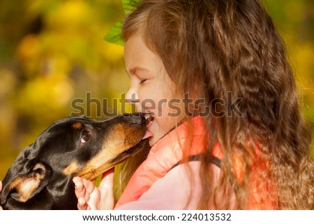 Little kid kissing dachshund puppy. Love to animals concept - stock photo