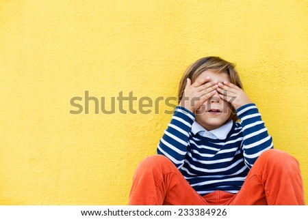 little kid on a yellow wall, wearing a stripes navy sweater, covering his eyes with his hands - stock photo