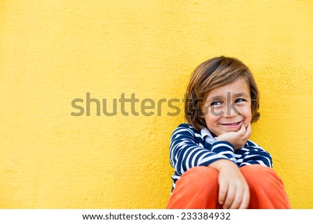 little kid on a yellow wall, wearing a stripes navy sweater, smiling and happy - stock photo