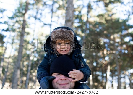 Little kid on father's shoulders - stock photo