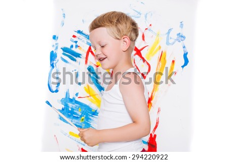 Little kid painting paints picture on easel. Education. Creativity. Studio portrait over white background - stock photo