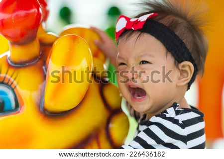 little kid playing in merry go round - stock photo