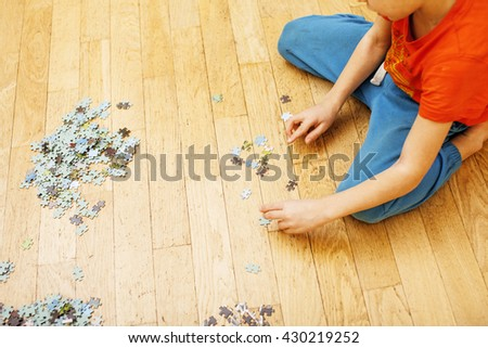 little kid playing with puzzles on wooden floor together with parent, lifestyle people concept, loving hands to each other - stock photo