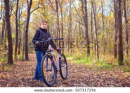 Little kid posing with his bicycle in the forest